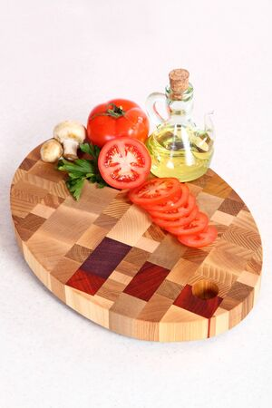 vegetable oil: the cut tomato, vegetable oil and field mushrooms on a chopping board