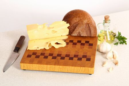 vegetable oil: The cut bread, cheese, parsley, garlic and vegetable oil on a chopping board Stock Photo