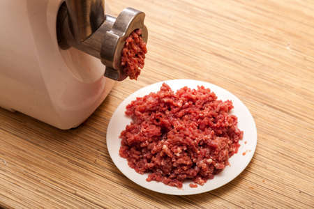 forcemeat: The electric meat grinder and forcemeat on a kitchen table