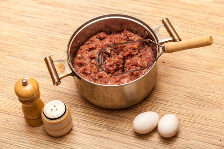 pepperbox: Mincemeat in a metal pan, eggs, a pepperbox and a saltcellar on a kitchen table Stock Photo