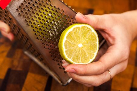 hand rubbing: the hand rubbing a lime on a grater Stock Photo