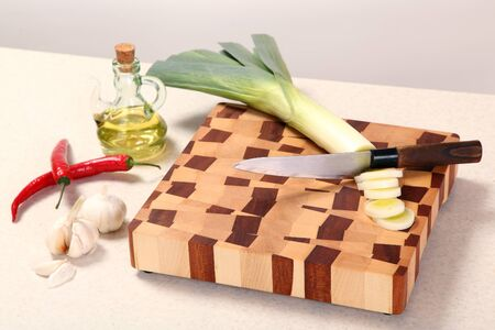 vegetable oil: leek knifed, garlic, vegetable oil, Chile on a chopping board Stock Photo