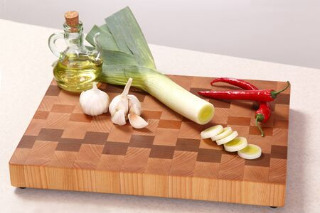 vegetable oil: leek, chili pepper, garlic and vegetable oil on a chopping board Stock Photo
