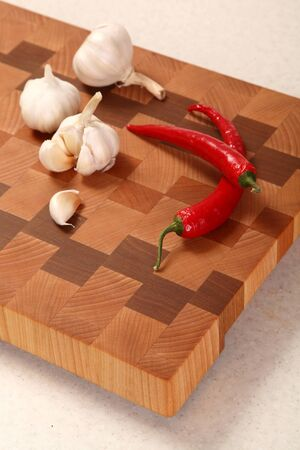 segmentar: segmento de ajo y dos chiles en una tajadera Foto de archivo