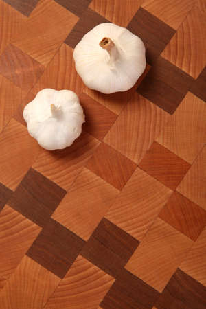 two heads: two heads of garlic on a chopping board