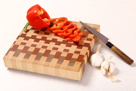 distribution board: pepper segments, garlic and a knife on a wooden chopping board