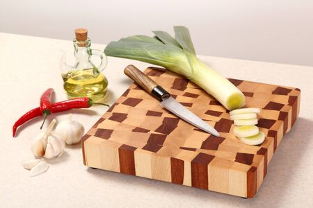 vegetable oil: the leek cut by segments, knife, Chile, garlic and vegetable oil on a chopping board Stock Photo