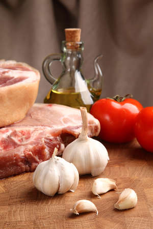 vegetable oil: pieces of pork, garlic, tomato and vegetable oil on a chopping board