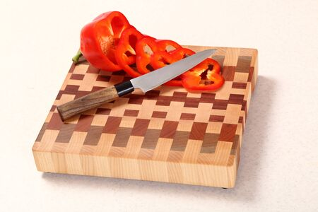 distribution board: segments of red pepper and a knife on a wooden chopping board