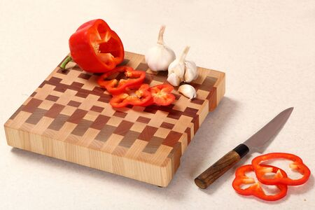 segments: segments of red pepper, garlic and a knife on a wooden choppingg board Stock Photo