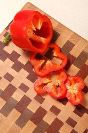 segments: segments of red pepper on a wooden chopping board