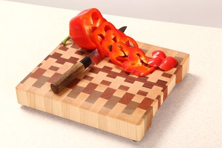food distribution: segments of pepper and a knife on a wooden chopping board