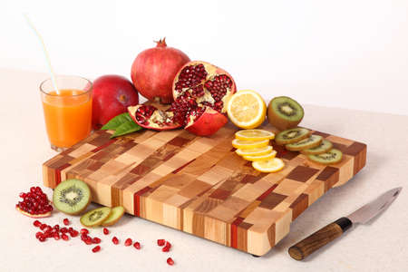 sweet segments: tropical fruit, knife and juice in a glass on a chopping board Stock Photo