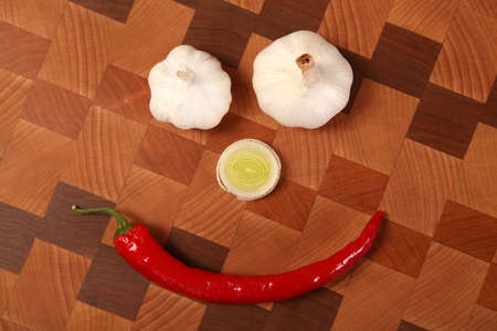 two heads: two heads of garlic, slice of a leek and chili pepper on a chopping board Stock Photo