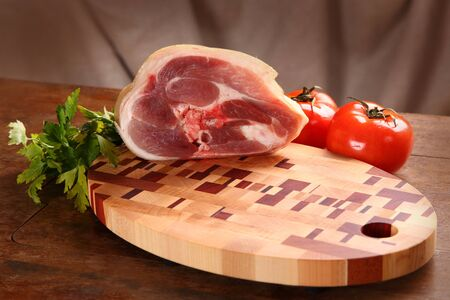 Meat, parsley and tomatoes on a chopping board photo