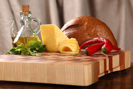 vegetable oil: Bread, cheese, Chile, vegetable oil and parsley on a chopping board Stock Photo