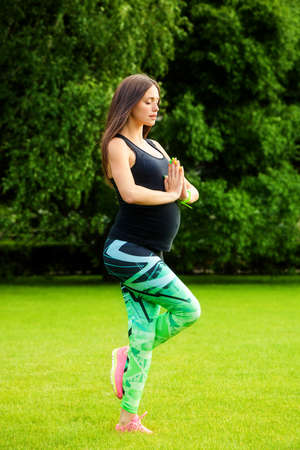 waiting posture: The pregnant young woman plays sports on a grass