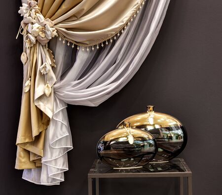 little table: The decorated gold curtain and little table with two vases Stock Photo