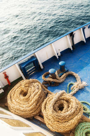 fleecy: Two old fleecy ropes curtailed into a spiral on the deck of the vessel