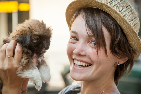 20 29: the young beautiful woman in a hat holds a little puppy in hand
