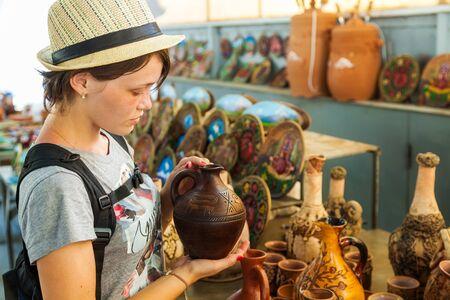 trabajo manual: la mujer joven y bella tiene en la mano una jarra trabajo hecho a mano en el día de apertura en Armenia