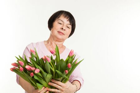 admires: the beautiful mature woman admires to a bouquet of tulips