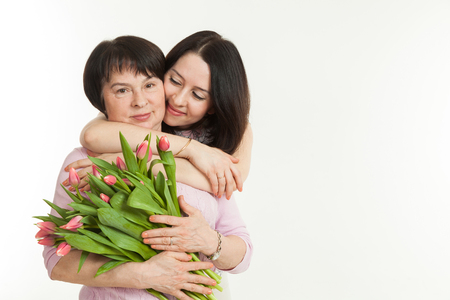 presented: the woman presented a bouquet of flowers for mother and embraces her