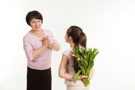 hides: the granddaughter hides a bouquet of flowers for the grandmother behind the back