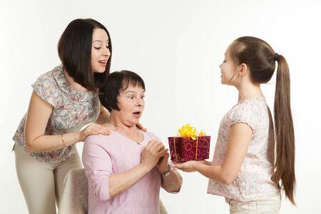 dar un regalo: la hija y la nieta dan un regalo a la abuela