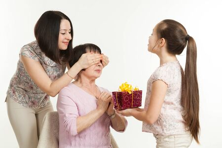 dar un regalo: the daughter and the granddaughter give a gift to the grandmother Foto de archivo