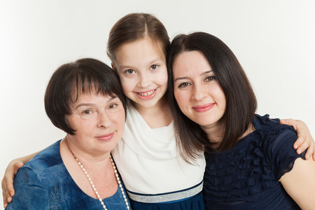 grandkid: The granddaughter embraces the grandmother and mother on a white background
