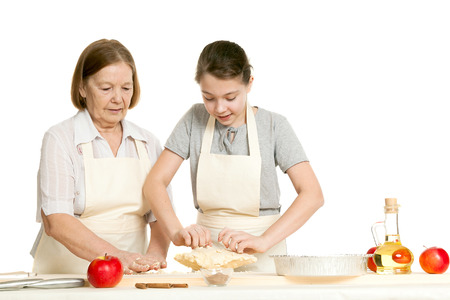 knead: the grandmother and the granddaughter knead dough on a kitchen table