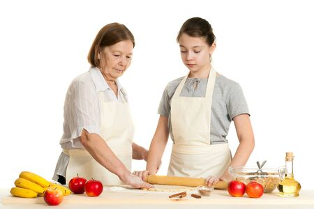 grandkid: the grandmother and the granddaughter roll dough with a rolling pin for pie on a white background