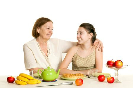 grandkid: the grandmother and the granddaughter sit at a table with the made pie