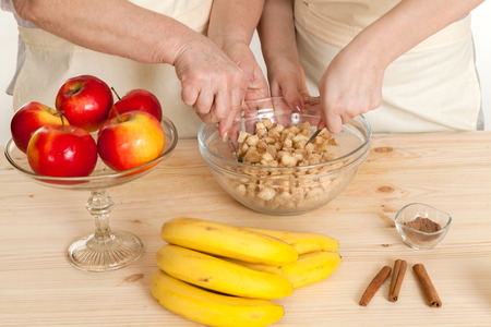 stir up: hands of the grandmother and hand of the granddaughter stir ingredients in a bowl a close up Stock Photo