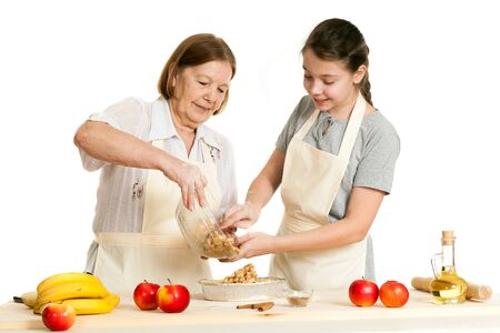 senior adults: the grandmother and the granddaughter stack a stuffing in a form for pie