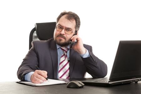 communicates: the businessman communicates by phone sitting at a table and makes entry Stock Photo