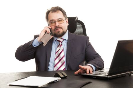 communicates: the businessman communicates by phone sitting at a table