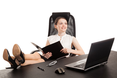 pensiveness: the business woman sits at office table with the laptop and reads the document Stock Photo