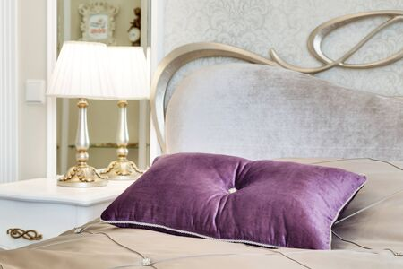 little table: little table with a lamp and a bed with pillows in a modern bedroom