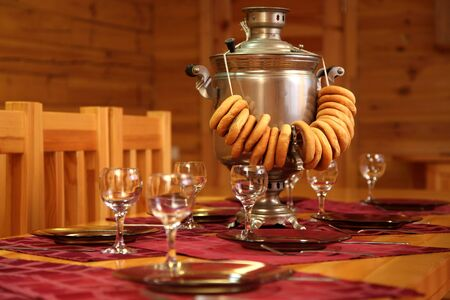 samovar: table with a samovar and ware indoors with wooden walls Stock Photo