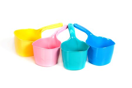 multi-colored plastic ladles on the white isolated background