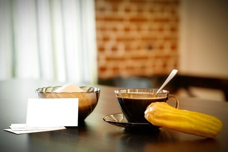 cup of coffee, eclair, sugar bowl and business cards on a table