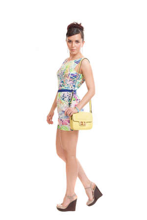 the young woman in convenient clothes with a bag on a white background