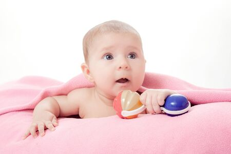the little beautiful baby under a pink plaid with a rattle in a hand Stock Photo