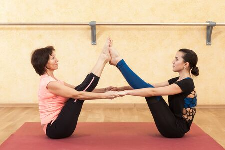 Young girl and mature woman doing yoga Stock Photo