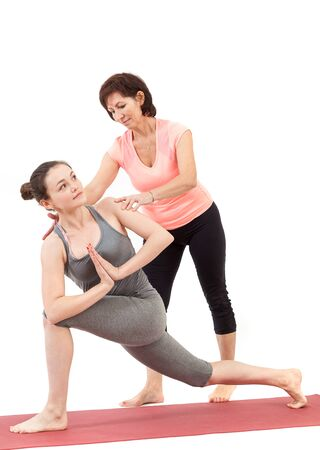 woman doing yoga under the guidance of a trainer