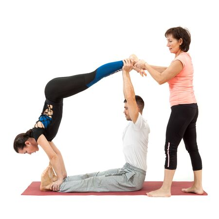 man and woman doing yoga under the guidance of a trainer Stock Photo
