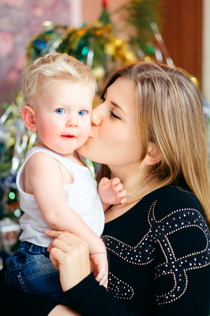Happy young mother holding her blue-eyed blond baby boy on hands and kisses him Stock Photo
