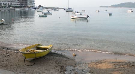 A boat on the shore of the bay near the fishermen village in the early morning photo
